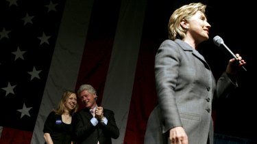 Former US president Bill Clinton and daughter Chelsea listen as presidential candidate Senator Hillary Clinton speaks at a fundraising rally in New York.