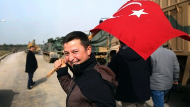 A civilian holding a Turkish flag arrives to encourage the troops at a Turkish army area on the border with Syria.