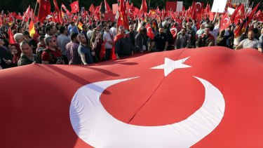 Protesters hold a national flag of Turkey in front of the Brandenburg gate in Berlin.