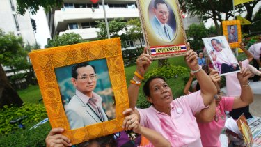 Thais hold portraits of King Bhumibol Adulyadej at Siriraj Hospital where the king is being treated in Bangkok.