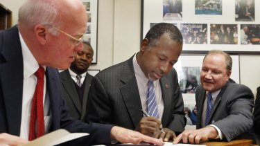 New Hampshire Secretary of State Bill Gardner (left) watches as Ben Carson gets help while filing papers to be on the nation's earliest presidential primary ballot on Friday.