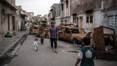 A man walks with his children past burnt out cars in a street in western Mosul, Iraq.