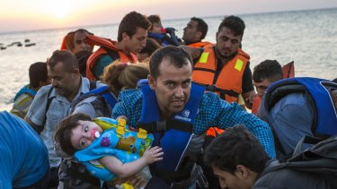 A man carries a girl as migrants arrive on a dinghy after crossing from Turkey to Kos on Thursday.