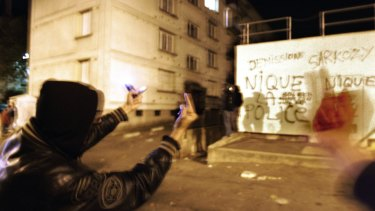 """Youths gesture next to a wall with graffiti  that reads """"F--- the police, Sarkozy resign"""", in the Renault housing complex of Les Mureaux, north-west of Paris, during the riots of 2005."""