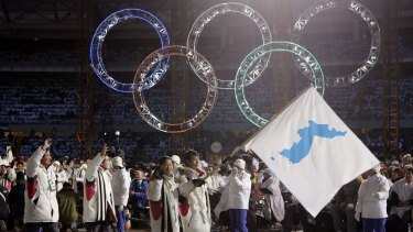 Korea flag-bearers carry a unification flag while leading their teams into the stadium during the 2006 Winter Olympics opening ceremony in Turin, Italy..