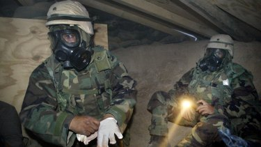 US soldiers in NBC (nuclear, biological, chemical) gear under torchlight in a bunker near camp Doha after a siren sounded a warning for a gas attack in Kuwait in 2003.