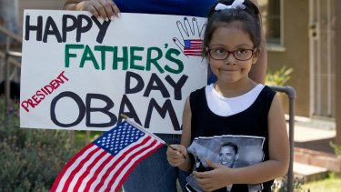Delilah Roldan, 5, stands with her mother Yvonne Roland, holding a sign wishing President Barack Obama a happy father's day as he drives past en route to an interview with comedian Marc Maron in California.
