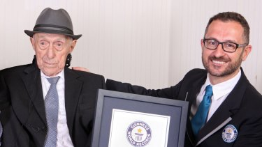 Marco Frigatti, from Guinness World Records, right, presents Israel Kristal a certificate for being the oldest living man.  The Auschwitz survivor is 112 years and 178 days old as of March 11.