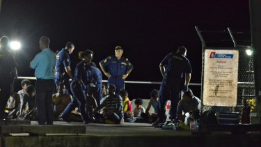 Customs officials and rescue personnel watch over survivors at Christmas Island after a boat capsized in July 2013.