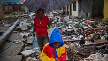A boy and a woman walk through houses destroyed by Hurricane Matthew in Baracoa, Cuba, on Wednesday.