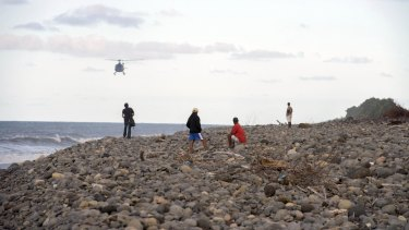 Helicopters search for debris: People walk on the beach of Saint-Andre, Reunion Island.