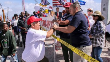 A President Donald Trump supporter, left, confronts a fellow Trump supporter, right, who was speaking on a megaphone, to stop being disrespectful and spewing hate.