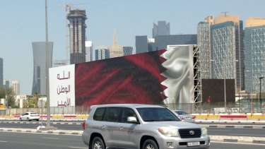 "A Qatari SUV drives past a billboard featuring the Qatari flag and the slogan ""God, Nation, Emir"" in Doha, Qatar, on Monday."