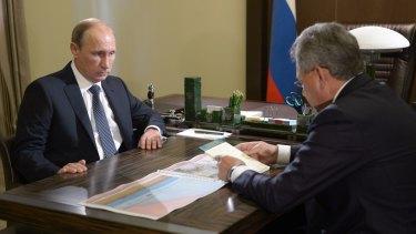 Russian President Vladimir Putin listens to Defence Minister Sergei Shoigu.