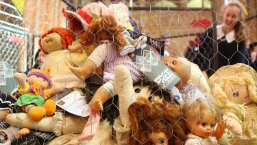 Children look at a cage filled with dolls inside  St John's Anglican Cathedral in Brisbane, representing the 895 child asylum seekers in detention.