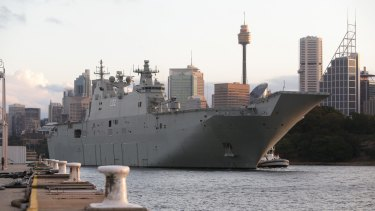 HMAS Canberra rounds the point of Garden Island as the ship sails out of Sydney Harbour.