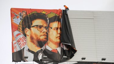 Shelved: Workers remove a poster for <i>The Interview</i> in Hollywood.