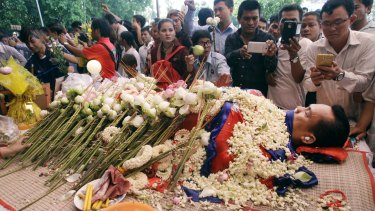 The body of government critic Kem Ley is covered by the Cambodian flag and flowers at a funeral ceremony in Phnom Penh.