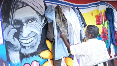 A man checks out a garment left at the Wall of Kindness in Bhilwara, India.