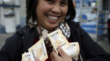 Zaida Cobangbang, of Union City, California, shows her Powerball tickets shortly after buying them on Saturday.
