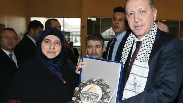 Turkish President Recep Tayyip Erdogan receives a picture of Jerusalem's Dome of the Rock from a Palestinian woman before addressing a symposium on Jerusalem in Istanbul in November.