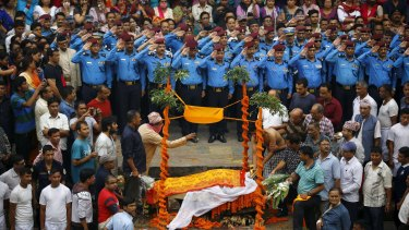 Nepali police officers salute as people watch  Laxman Neupane's son (right) cremate his father.