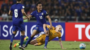 Teerasil Dengda of Thailand tackles the Socceroos' Aaron Mooy during the 2018 FIFA World Cup Qualifier.
