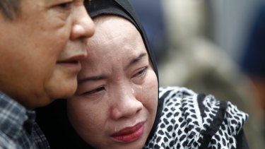 Family members cry outside an Islamic religious school on the outskirts of Kuala Lumpur following a fire on Thursday.