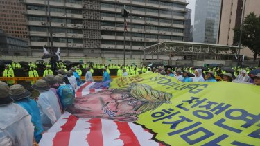 Protesters march in front of the US Embassy after a rally in Seoul demanding peace on the Korean peninsula.