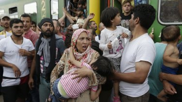 A woman carrying a child stands outside a train with migrants that was stopped in Bicske, Hungary, on Thursday.