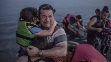 A Syrian refugee from Deir Ezzor, holding his son and daughter, breaks out in tears of joy after arriving via a flimsy inflatable boat crammed with about 15 men, women and children on the shore of the island of Kos in Greece.