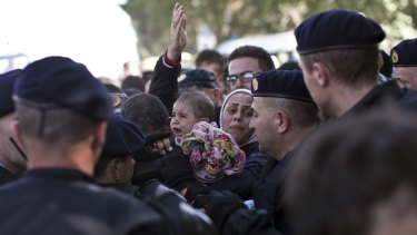 A baby cries as a family tries to push through a police line in Tovarnik, Croatia, on Thursday.