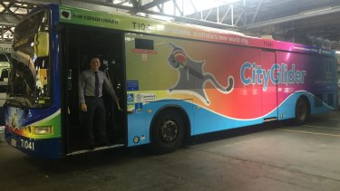 Brisbane City Council's public transport chairman Peter Matic with the Brisbane Pride Festival-themed rainbow bus. A resident has complained about advertising restricting the view from inside the bus.