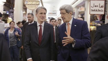 US Secretary of State John Kerry, right, and British Foreign Secretary Philip Hammond walk through the Quincy Market food court after visiting the Wind Technology Testing Centre.