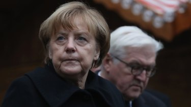 German Chancellor Angela Merkel and Foreign Minister Frank-Walter Steinmeier lay flowers at the Berlin Christmas market where 12 people died after a truck ploughed onto the crowd.
