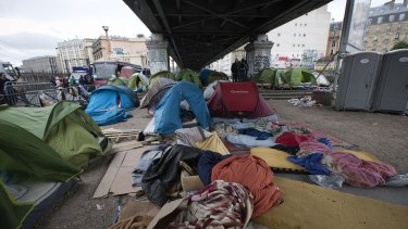 Police officers stand in the makeshift camp under a railway bridge in northern Paris.