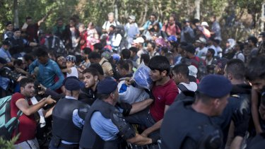 Migrants push through a police line in the eastern Croatian town of Tovarnik, with people trampling and falling on each other amid the chaos.
