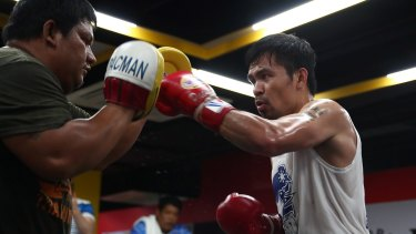 Workout: Manny Pacquiao works the pads with Buboy Fernandez at the Elorde boxing Gym in Manila on Thursday.