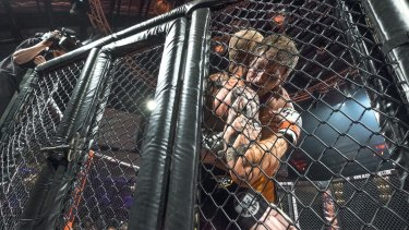 Ryan Barry, left, battles Troy Resic at Victoria's first legal MMA cage fight last night.