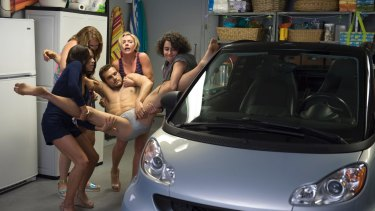 The women have to wrangle a dead stripper (Ryan Cooper).