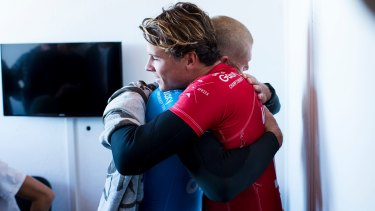 Ordeal over: Julian Wilson hugs Mick Fanning from the safety of shore.