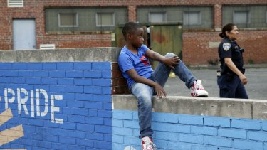 A boy sits on a wall as a Baltimore police officer walks by  near the site of unrest following the funeral of Freddie Gray.