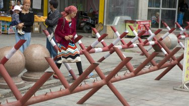 Uighur women walk past barricades set up at the entrance to a shopping district in the city of Aksu in western China's Xinjiang province in 2014.
