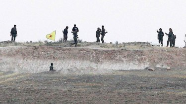 Kurdish People's Protection Units (YPG) fighters take position in the northern Syrian town of Tel Abyad on Monday.