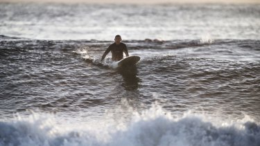 Tony Abbott sits on his long board before taking off on a wave at North Steyne in 2014.