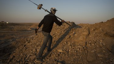 A Chinese surveyor climbs to take measurements at the site of a bridge project near Shymkent, Kazakhstan.