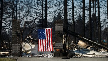 An American flag hangs on a burnt home in Santa Rosa on Sunday.