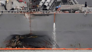The damaged port aft hull of the USS John S. McCain, is visible while docked at Singapore's Changi naval base on Tuesday.