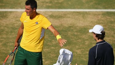Tough day: Bernard Tomic throws his towel back during his Davis Cup loss to John Isner.