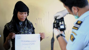 Mukharramah, a rescued Rohingya woman from Myanmar, has her photograph taken by Indonesian immigration personnel following arrival at the fishing town of Kuala Cangkoi in Aceh province.